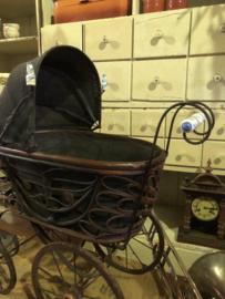 Antieke kinderwagen met porselein