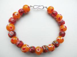 Oranje/rode kralen bracelet met zilveren sluiting.
