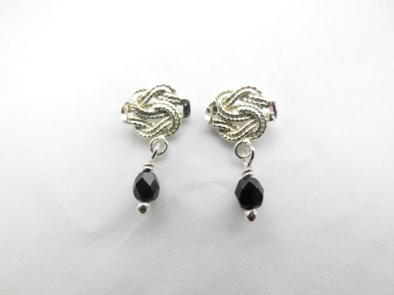 Zilveren mattenklopper oorknoppen met zwart kraaltje.