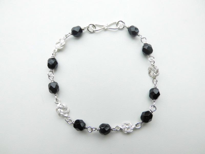 Zilveren mattenkloppertjes zwarte kralen bracelet.