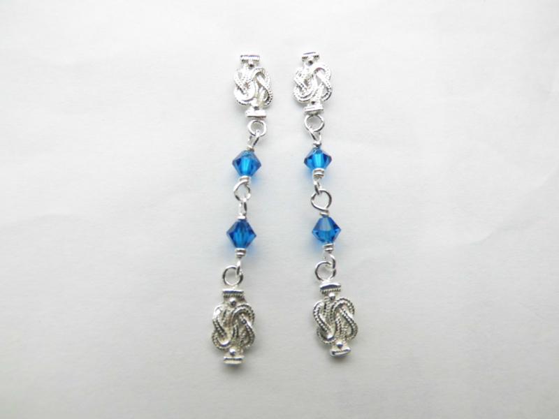 Zilveren mattenklopper blauwe kralen oorbellen.
