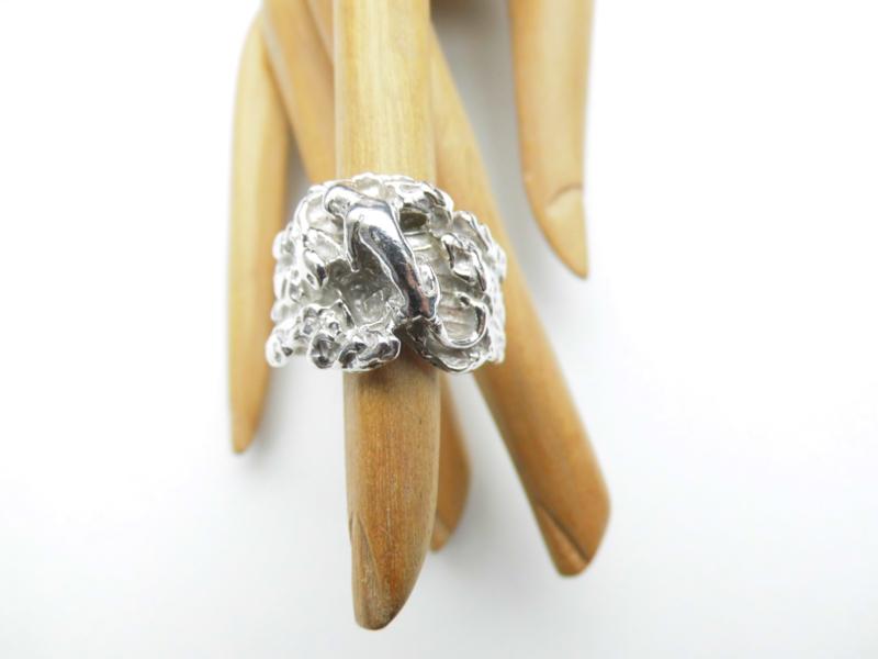 Zilveren rots ring met kleine pantertje erop.