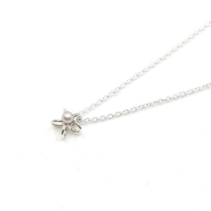 Zilveren collier met bloem en grijze parel.