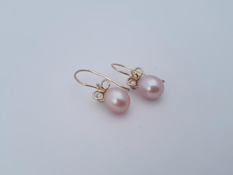 Zilveren oorbellen met roze parel.