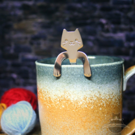 Cat teaspoon that looks over the edge of a cup
