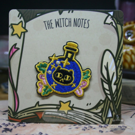 Embroided clothing patch of a potion bottle with cat head