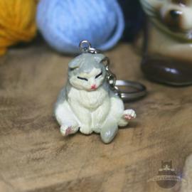 Schlüsselanhänger sitzende weißgraue Katze