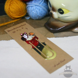 Enameled bookmarker of a reading black and white cat