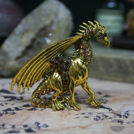 Gold colored dragon brooch decorated with stones