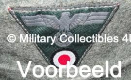 Het aanbrengen van 1 insigne op een pet of uniform