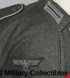 Het aanbrengen van 2 Heer of SS m40 kraagspiegels en 1 adelaar op een jas