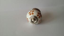 wit kast- of deurknopje met bruine bloemen.