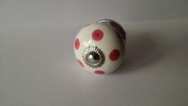 wit kast- of deurknopje met roze stippen.