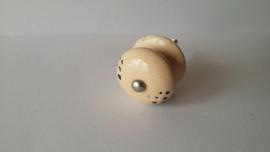 zalmkleurig kast- of deurknopje met zwarte stippen.