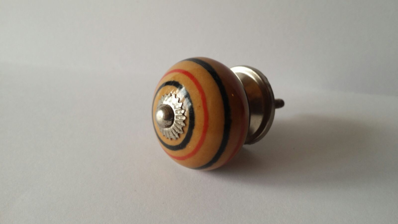 bruin kast- of deurknopje met rode en zwarte ringen.