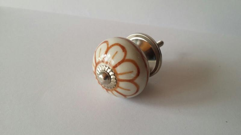 wit kast- of deurknopje met bruine bloem.