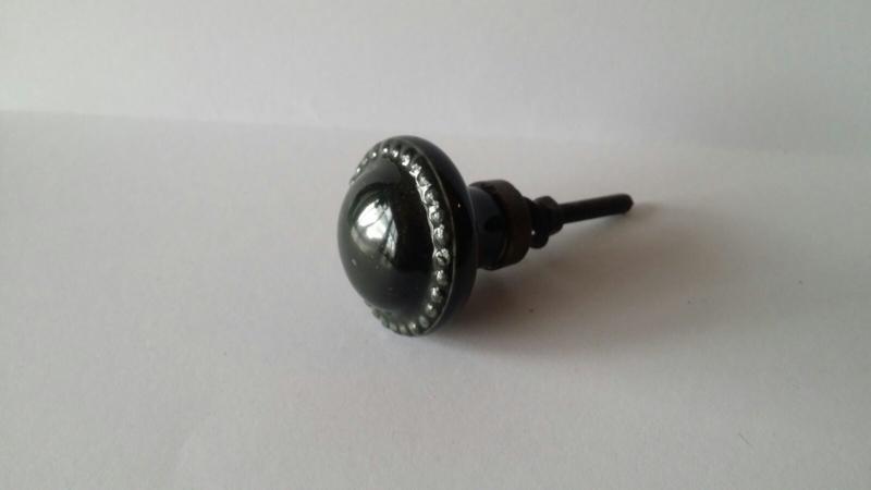 donkergroen/zwart kast- of deurknopje met geribbelde rand.