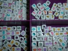Mooie witte cijferkralen met gekleurde cijfers in de vorm van een blokje