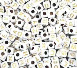 Witte letterkralen met gouden letters in de vorm van een blokje