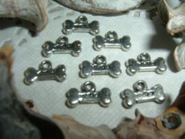 Mooie kleine zilverkleurige bedeltjes in de vorm van een hondenbotje