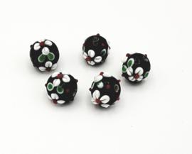 Mooie ronde zwarte glaskralen met witte opgelegde bloem van 11 mm.