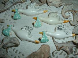 Vliegende ooievaartjes met baby in blauwgroene draagdoek