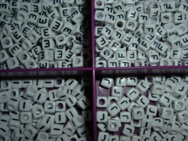 Mooie witte letterkralen met zwarte letters in de vorm van een blokje