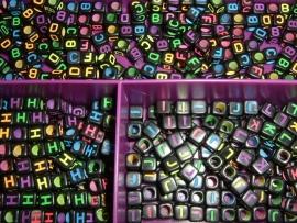 Mooie zwarte letterkralen met neon letters in de vorm van een blokje