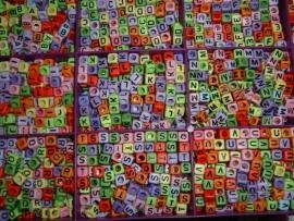 Mooie vrolijke gekleurde letterkralen in de vorm van een blokje