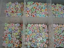 Mooie gekleurde letterkralen in de vorm van een klein hartje