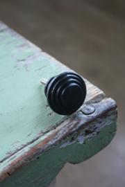 ronde zwarte metalen knop met lijntjes