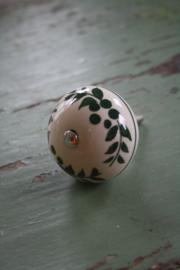 porseleinen knop met groene blaadjes