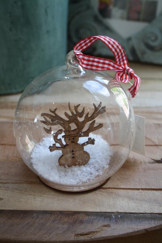 grote glazen bal met sneeuw en houten sneeuwpop