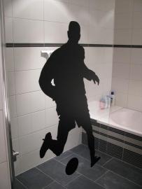 voetbalsticker op het doucheraam geplakt