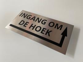 """RVS deurplaatje, opschrift """"INGANG OM DE HOEK"""" + pijl rechstom 18x9cm"""