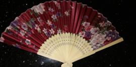 Mooie handwaaier met bloemen van bamboe en stof donkerrood