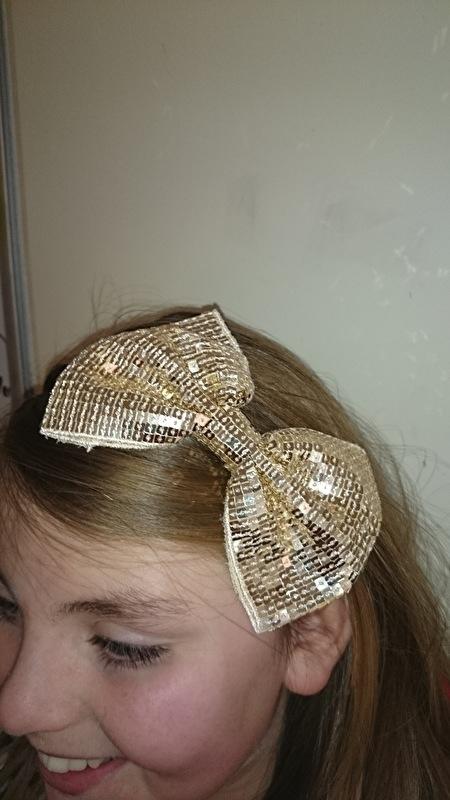 Leuke haarband met grote glitterstrik goud