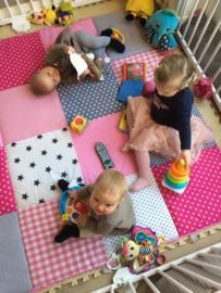 Een superblije tweeling op een speelkleed