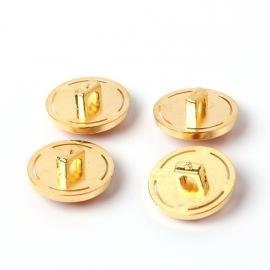 Goudkleurige knoop met gele steen