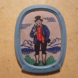 1938-11-5/6 Winter Relief donation pin. Traditional dress Austria / Ostmark - Tyrol , man with pipe. Woven fabric in metal frame 44x33mm T157.1 (13530)