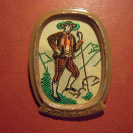 1938-11-5/6 German WHW donation pin. , Traditional dress Austria / Ostmark -  Tyrol , man with cane. Woven fabric in metal frame  T156.1 (9669)