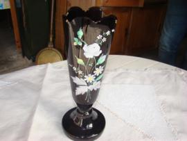 Zwarte glazen vaas op voet met geschilderde bloemen.