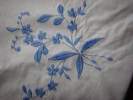 Wit geborduurd kleedje met blauwe bloemen.