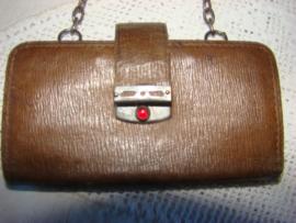 Oude leren portemonnee met rode steentjes en ketting.