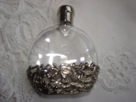 Parfumflesje met zilverkleurige schroefdop en onderrand met dotters.