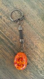 Oranje spikkelkraal aan bronskleurige sleutelhanger