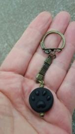 Zwarte pootjeskraal aan bronskleurige sleutelhanger