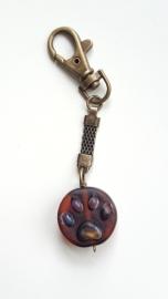 Bruine pootjeskraal aan bronskleurige sleutelhanger
