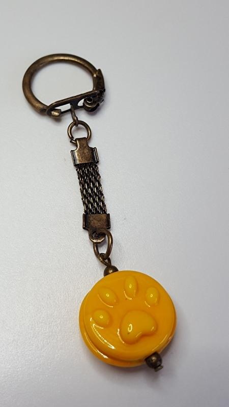 Gele pootjeskraal aan bronskleurige sleutelhanger