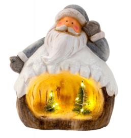 Kerstman met verlichte dennenbomen